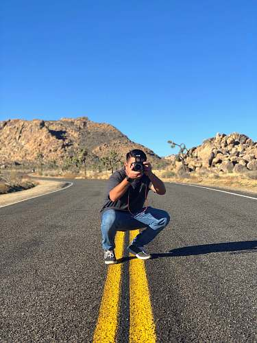 person man sitting in road taking picture asphalt