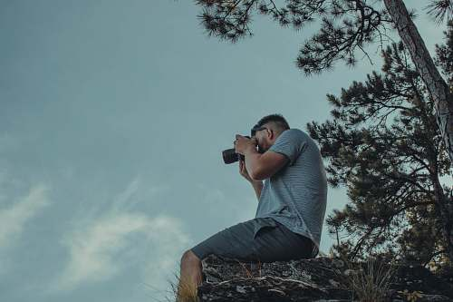 photo person man sitting on cliff while taking picture photography free for commercial use images