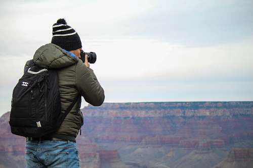 photo person man taking photo of rock formation outdoors free for commercial use images