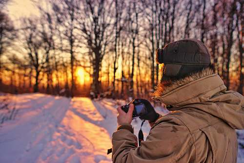 photo person man wearing brown jacket holding black camera photographer free for commercial use images