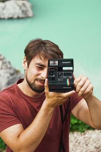 person man wearing maroon crew-neck shirt holding black Instant Polaroid camera photo