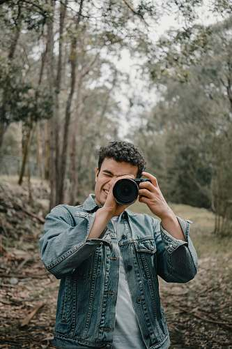 person man wears blue denim jacket camera