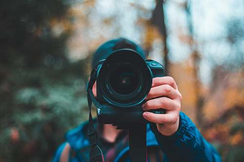 photo photographer selective focus photography of man holding black DSLR camera camera free for commercial use images