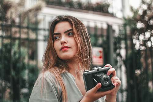 photo person selective focus photography of woman wearing gray top holding camera camera free for commercial use images