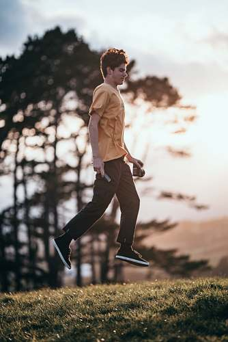photo apparel shallow focus photo of man in brown T-shirt jumping clothing free for commercial use images
