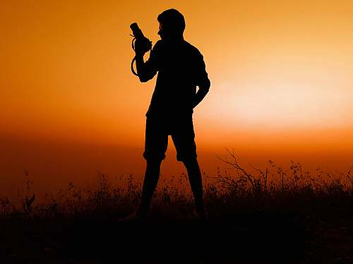 person silhouette of man holding pistol photo