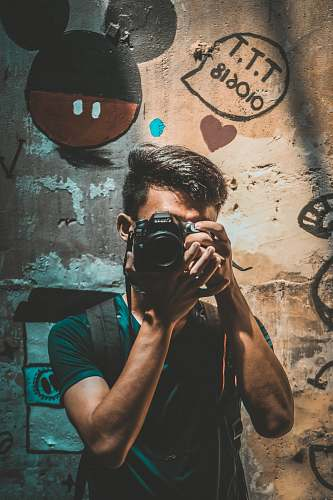 photo person unknown person holding black Canon DSLR camera camera free for commercial use images