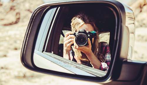 person woman holding DSLR camera facing side mirror mirror