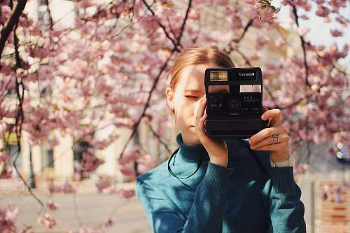 photo person woman holding Polaroid land camera blossom free for commercial use images