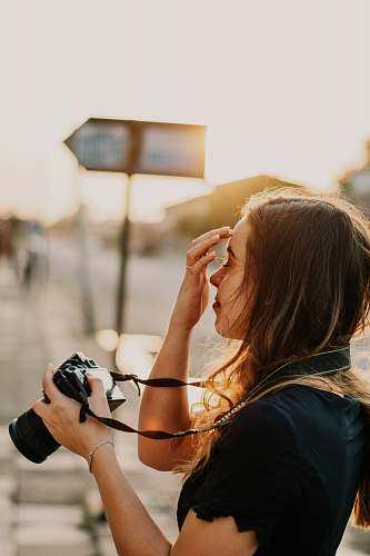 photo person woman in black shirt holding DSLR camera photographer free for commercial use images