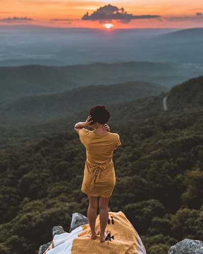 person woman in brown dress standing on cliff overlooking forest during golden hour outdoors