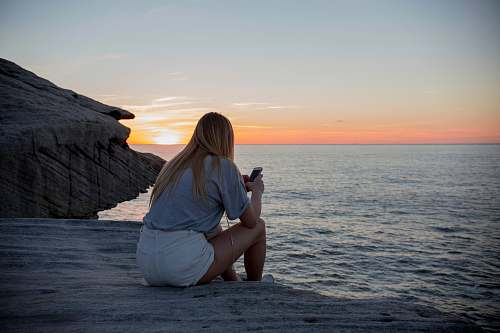 photo person woman in grey shirts and white sorts sits on rock cliff by the beach photo free for commercial use images