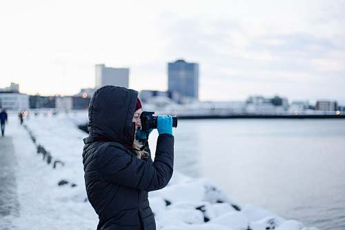 photo person woman wearing black hooded jacket using DSLR camera photographer free for commercial use images