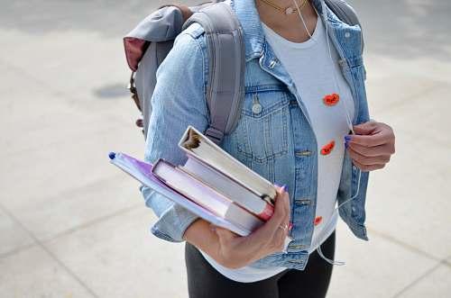 school woman wearing blue denim jacket holding book people