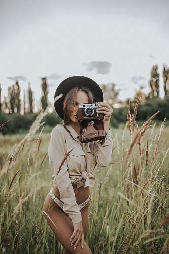 photo person woman wearing white pantie holding gray and brown camera plant free for commercial use images