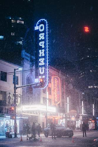 outdoors people walking near lighted buildings at nighttime snow