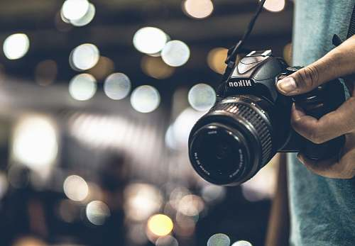 photo camera bokeh photography of person holding Nikon DSLR camera with strap electronics free for commercial use images