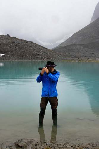 photo human man standing on body of water using DSLR camera apparel free for commercial use images