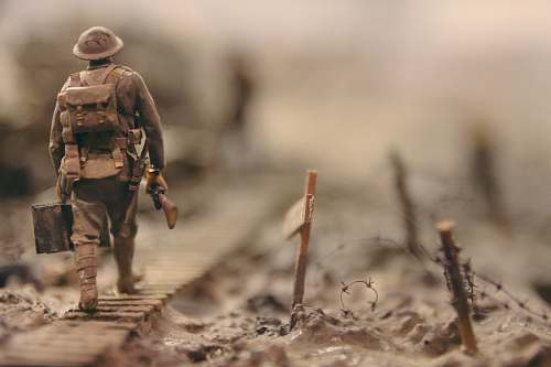 human soldier walking on wooden pathway surrounded with barbwire selective focus photography people