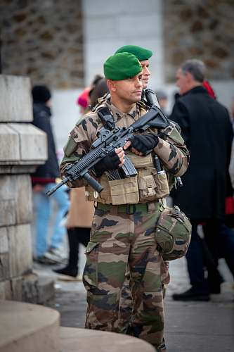 human soldier with rifle stands guard in front of building gun
