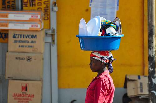 human woman in red collared top carrying basin on head people