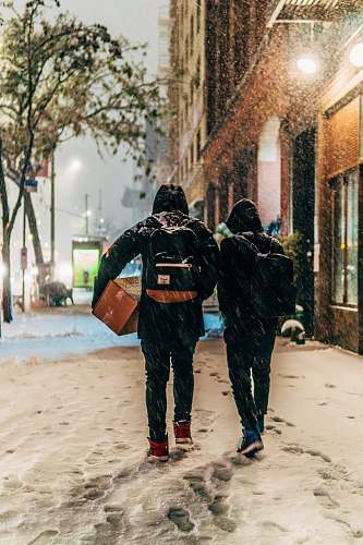 photo winter two people walking beside brown concrete building during snow storm free for commercial use images