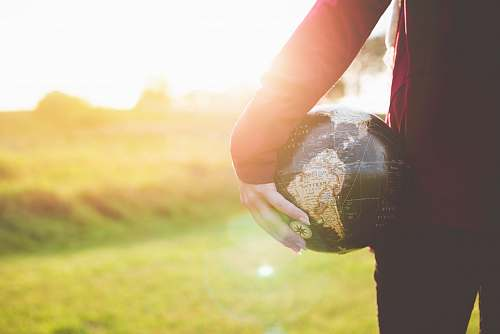 photo world person holding black and brown globe ball while standing on grass land golden hour photography hand free for commercial use images