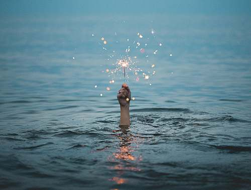 sparkle person submerged on body of water holding sparkler holding