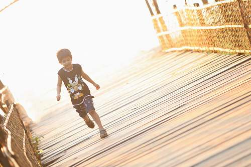 person boy walking on brown wooden bridge people