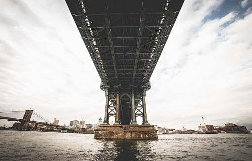 building grey steel bridge over sea under grey and blue sky under bridge