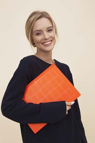 apparel smiling woman standing while holding orange folder sleeve