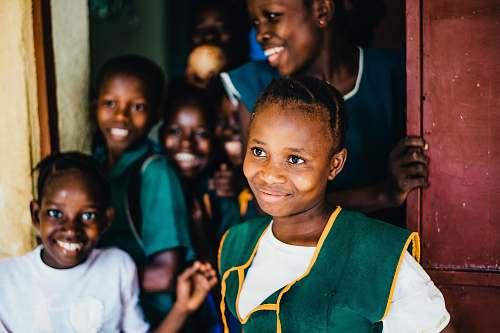 person children smiling while standing near open door happy school