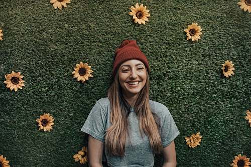 apparel smiling woman leaning on floral wall clothing