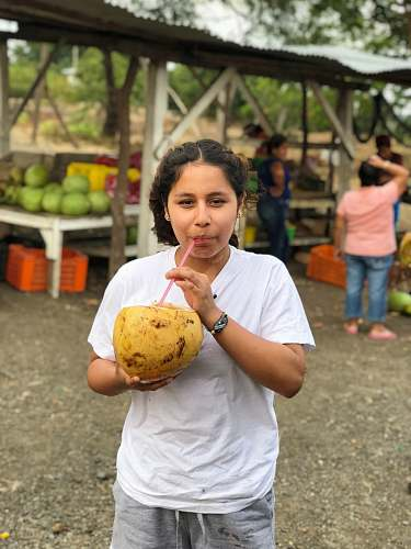 person woman sipping coconut fruit people
