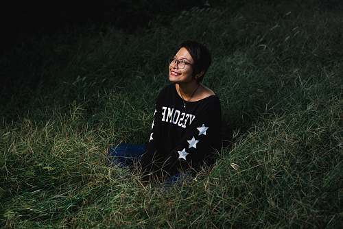 person woman sitting on grass smiling and looking up during nighttime people