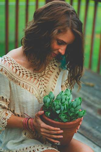 person woman sitting while holding pot of succulent plants people