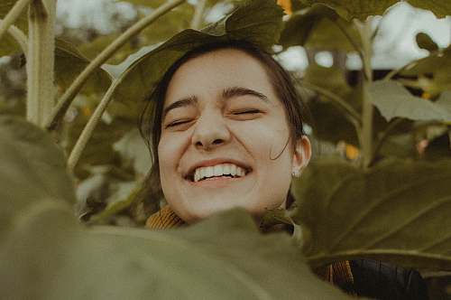 person woman smiling between plants people