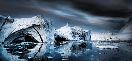 glacier snow capped mountain near body of water under gray clouds outdoors
