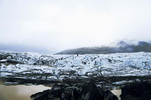 glacier snow covered rocky field near body of water during daytime snow