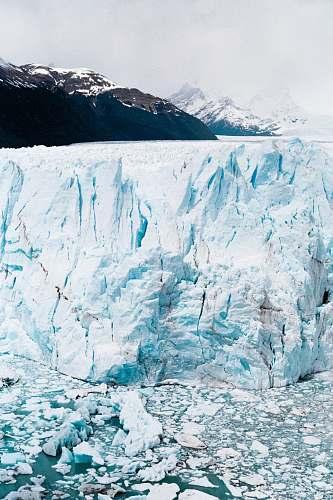 ice iceberg near mountain at daytime snow