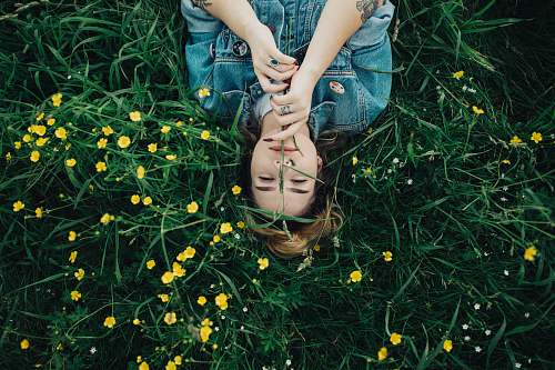 human woman lying on grass ground with yellow petaled flowers person