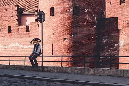 human man sitting on metal rails brick