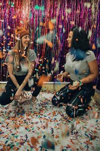 confetti two women kneeling under falling confetti paper