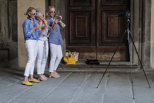 photo clothing three women standing while holding ice cream beside building footwear free for commercial use images