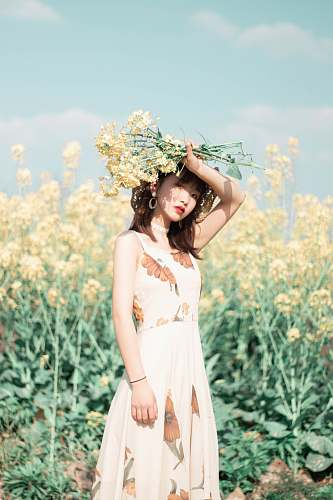 clothing woman holding yellow-petaled flowers above her head gown