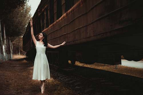 photo apparel woman wearing white dress dancing beside train fashion free for commercial use images