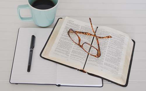 bible flat lay photography of tortoiseshell eyeglasses on top of book near black pen and teal mug glasses