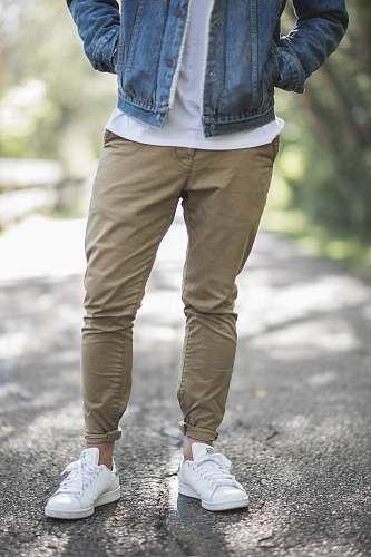 photo man man wearing brown fitted jeans and sneakers standing on road at daytime male free for commercial use images