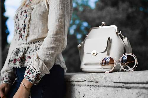 photo human woman wearing beige and red floral top leaning on gray concrete slab with white leather bag ontop person free for commercial use images