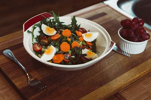 vegetable bowl of salad with slide of cooked egg with grapes on the side plate